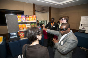 Kevin Irick, right, demonstrates his visual assistance eyepiece to a exhibition attendee.