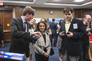 Gus Smith, left, demonstrates his visual assistance smart glove to France Cordova, NSF Director. Peter Zientra, right, looks on.